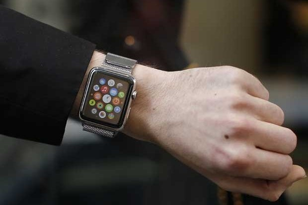 A customer presents his Apple Watch after buying it at a store.