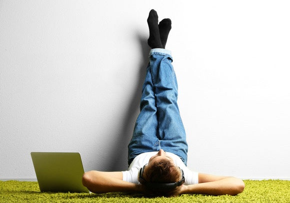 Guy in jeans laying upside down against wall with laptop