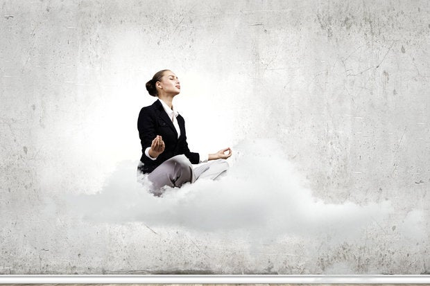 Woman meditating on cloud in bare room
