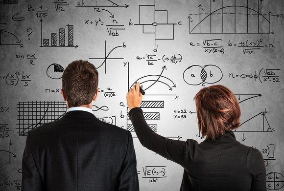 male and female executives facing wall working on analytics