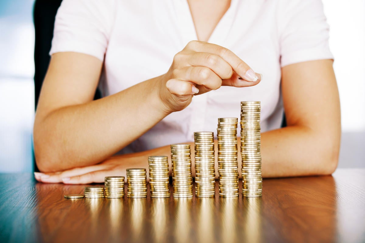 A woman stacking gold coins.
