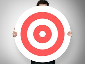 young man standing behind large red bullseye target