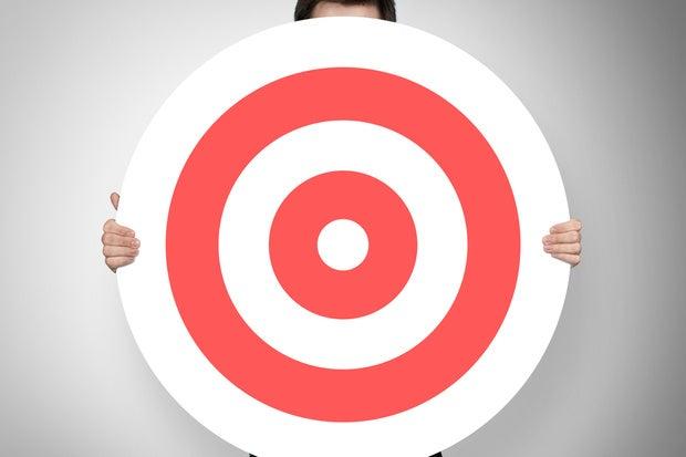 young man standing behind large red bullseye target