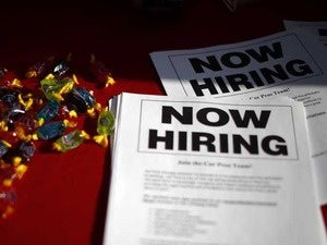 Leaflets that say Now Hiring lie on a table at a job fair