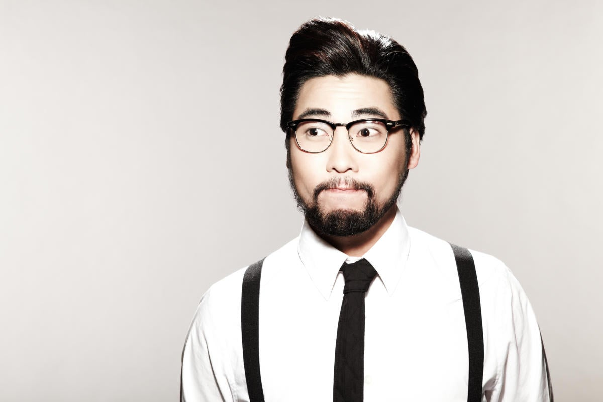 Young asian hipster in suspenders looking surprised or confused