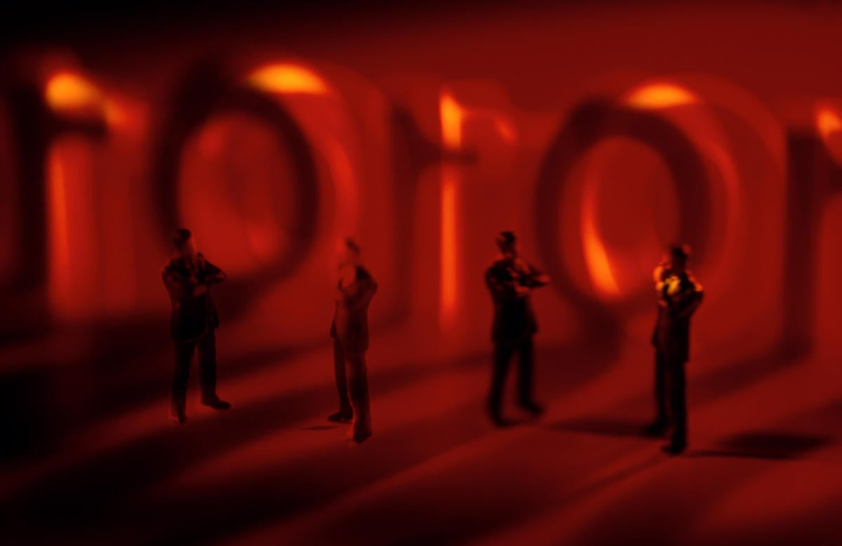 conceptual image with red background and miniature people standing in front of code