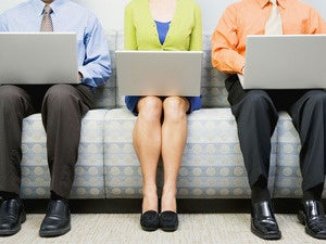 row of three men and women seated on couch with laptops waiting for interview