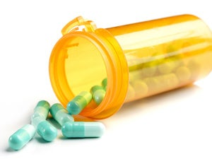yellow pill bottle with green pills spilling out