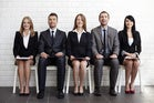Row of diverse young executives seated on chairs waiting for job interview