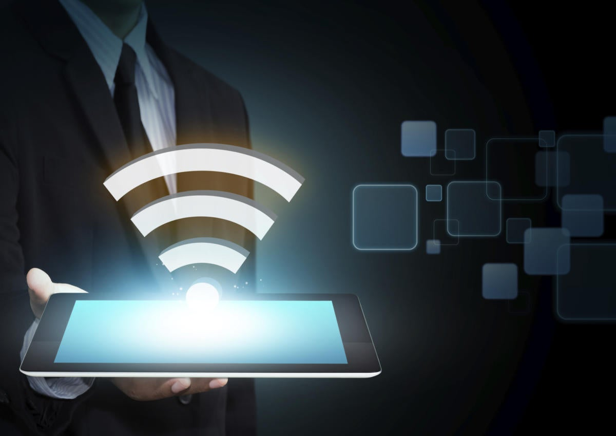 Male executive holding tablet with hovering wireless icon