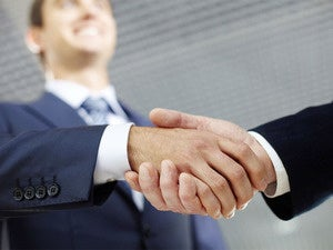 two businessmen shaking hands making a deal