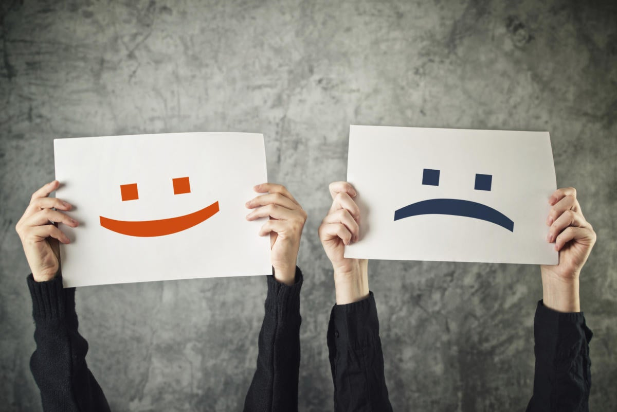 emoticon signs being held by 2 people