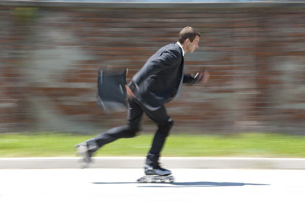 agile male executive on roller blades holding briefcase in motion