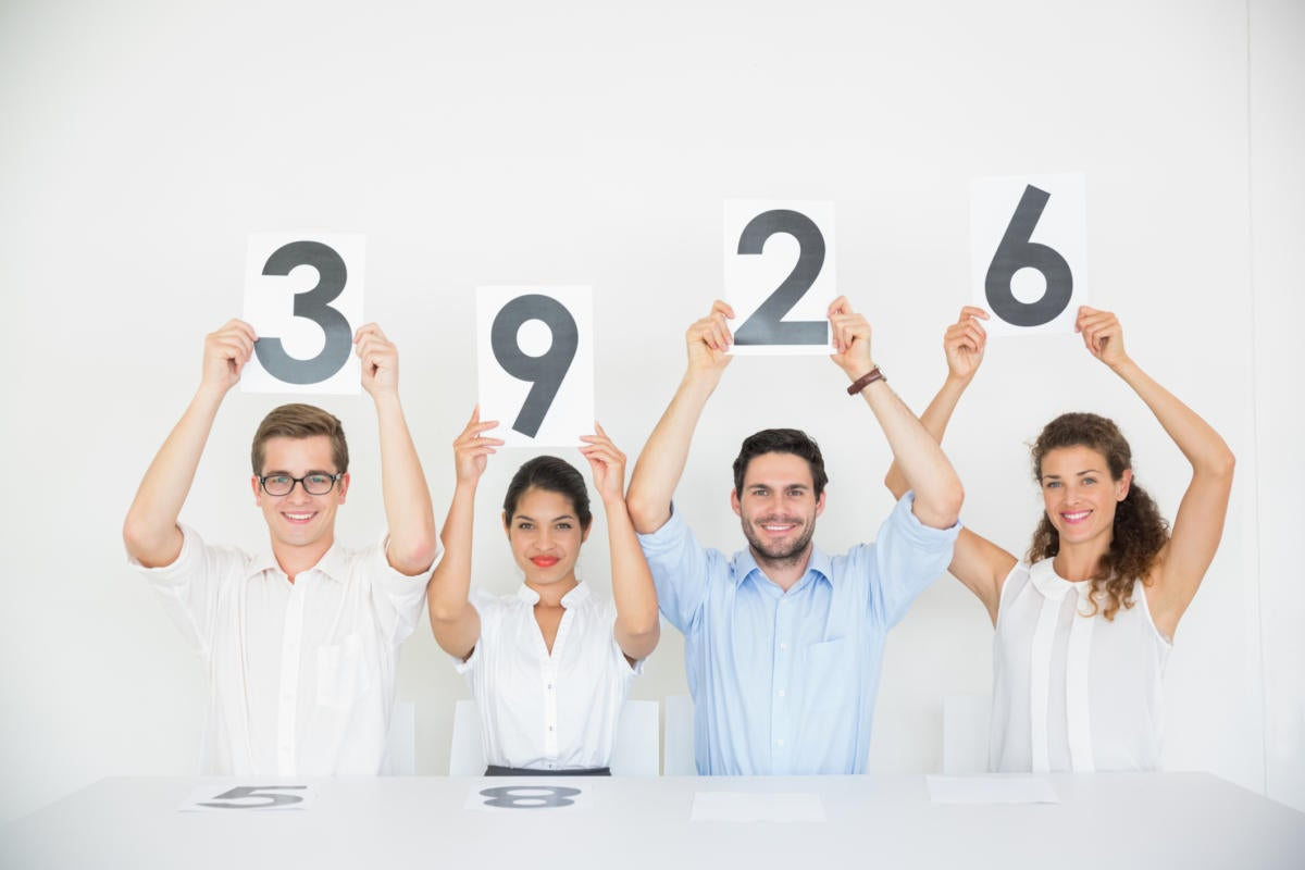 diverse group of millennials holding up score card numbers