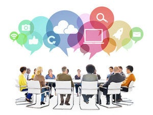 diverse group of people seated in a circle collaborating with social media icons floating above them