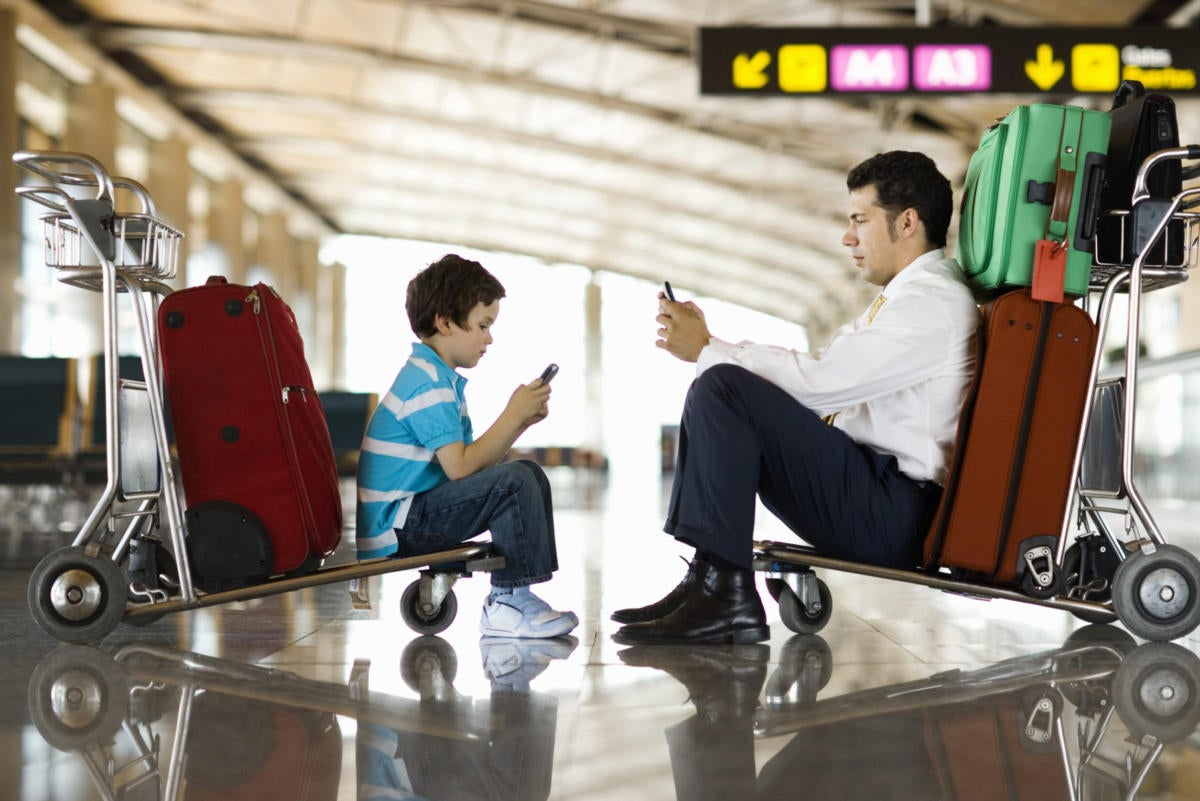 Man and boy in airport using wireless or cellular phones