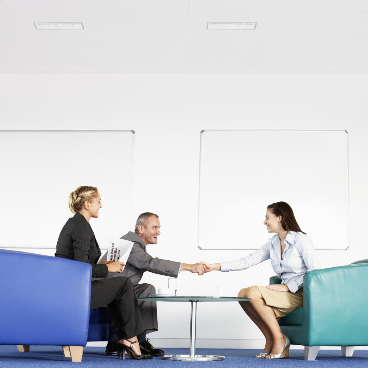 3 male and female executives sitting in office shaking hands and interviewing