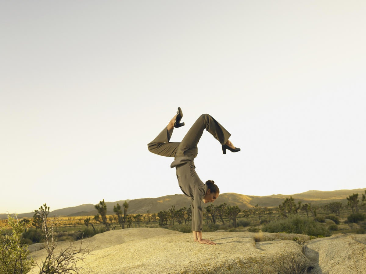 Woman in desert doing handstand showing agility