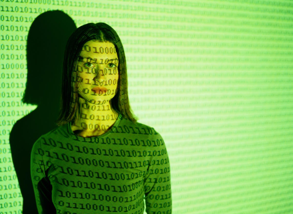 young woman in green with binary code projected on top of her