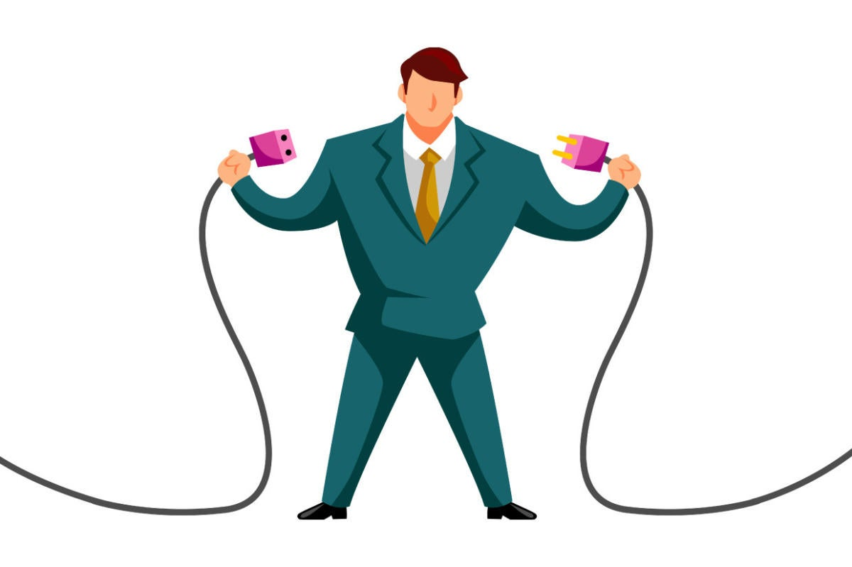 A businessman connects two power cords.