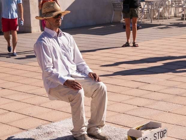 A street performer sitting on an invisible chair