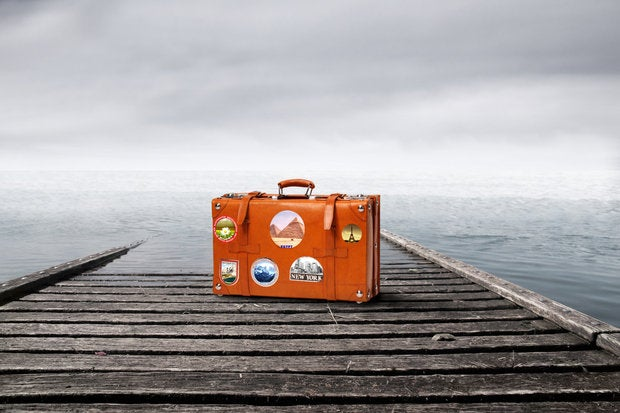 outsourcing suitcase with travel stickers at edge of dock