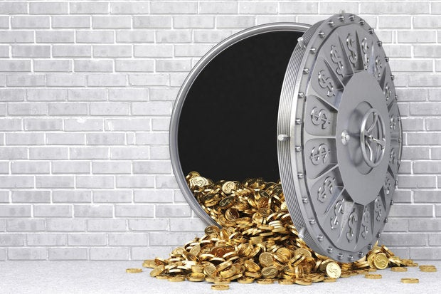 Open bank vault with gold coins spilling out