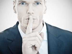 handsome male executive holding finger up to be quiet keep a secret