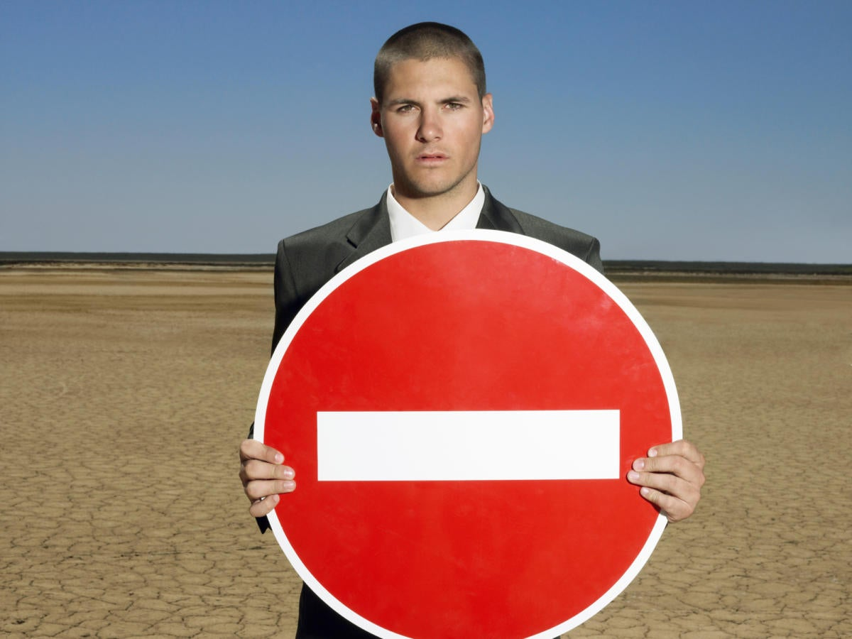 young man in suit on the beach holding red do not enter sign