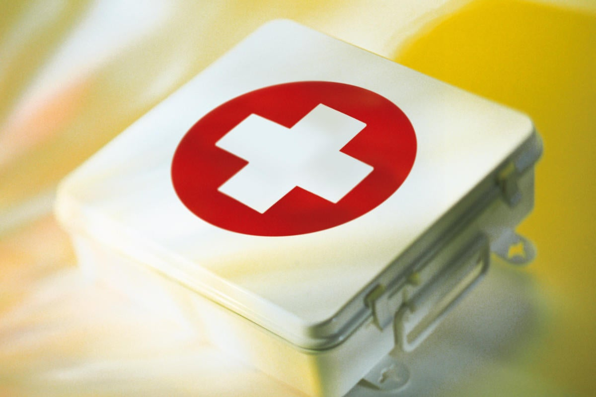 white first aid kit with red medical icon on yellow background