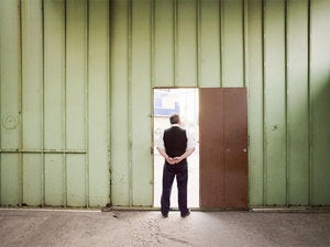 Man standing in open doorway in large empty green warehouse