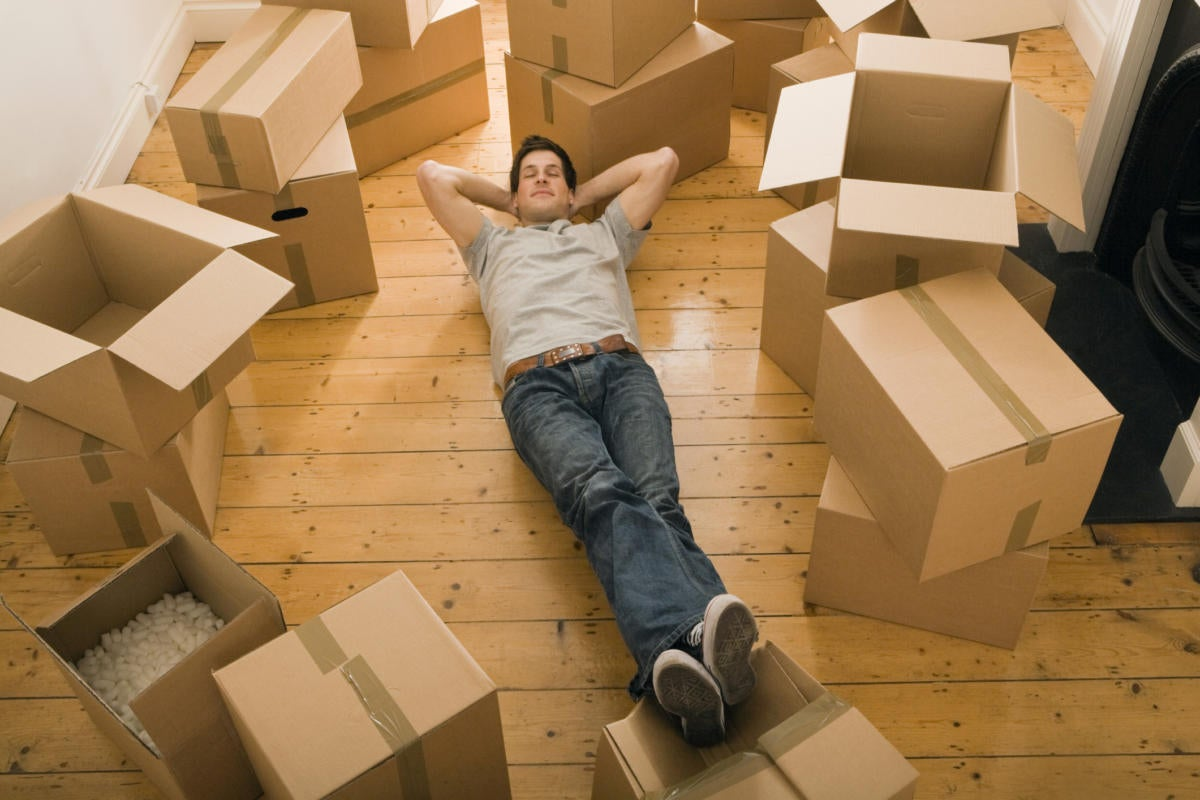 Young man laying on ground surrounded by empty moving boxes