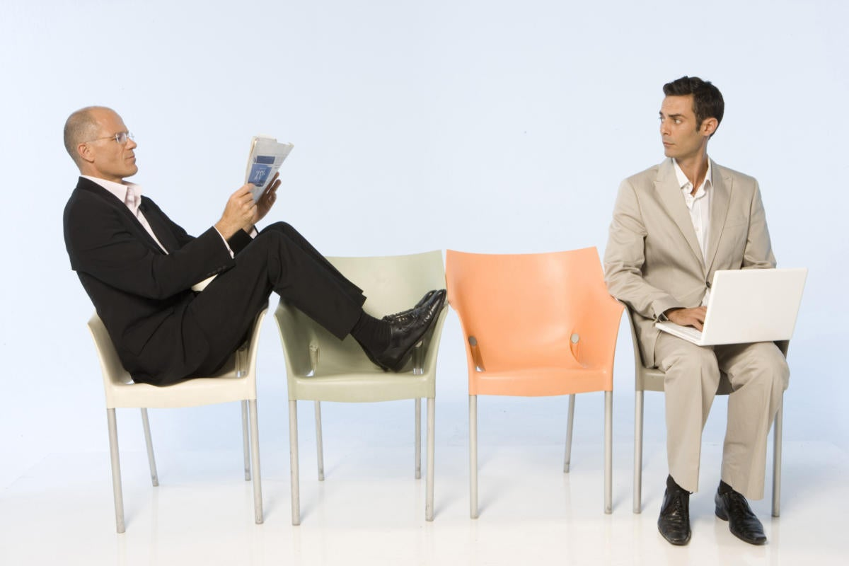 two business men sitting in chairs waiting for interview