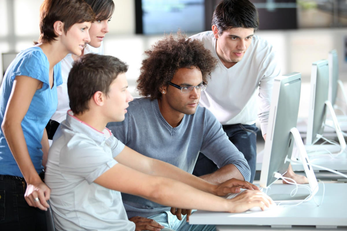group of millennials working together looking at computer