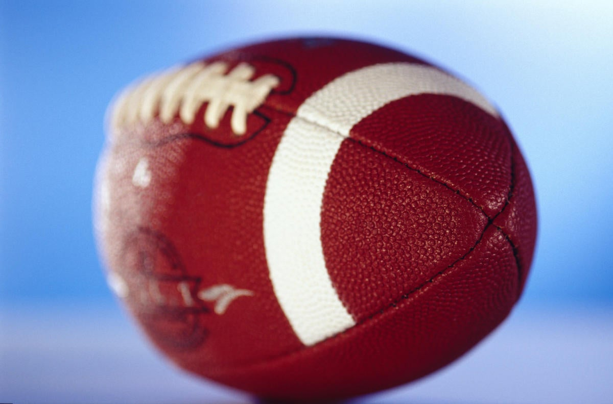 Football in soft focus against blue background