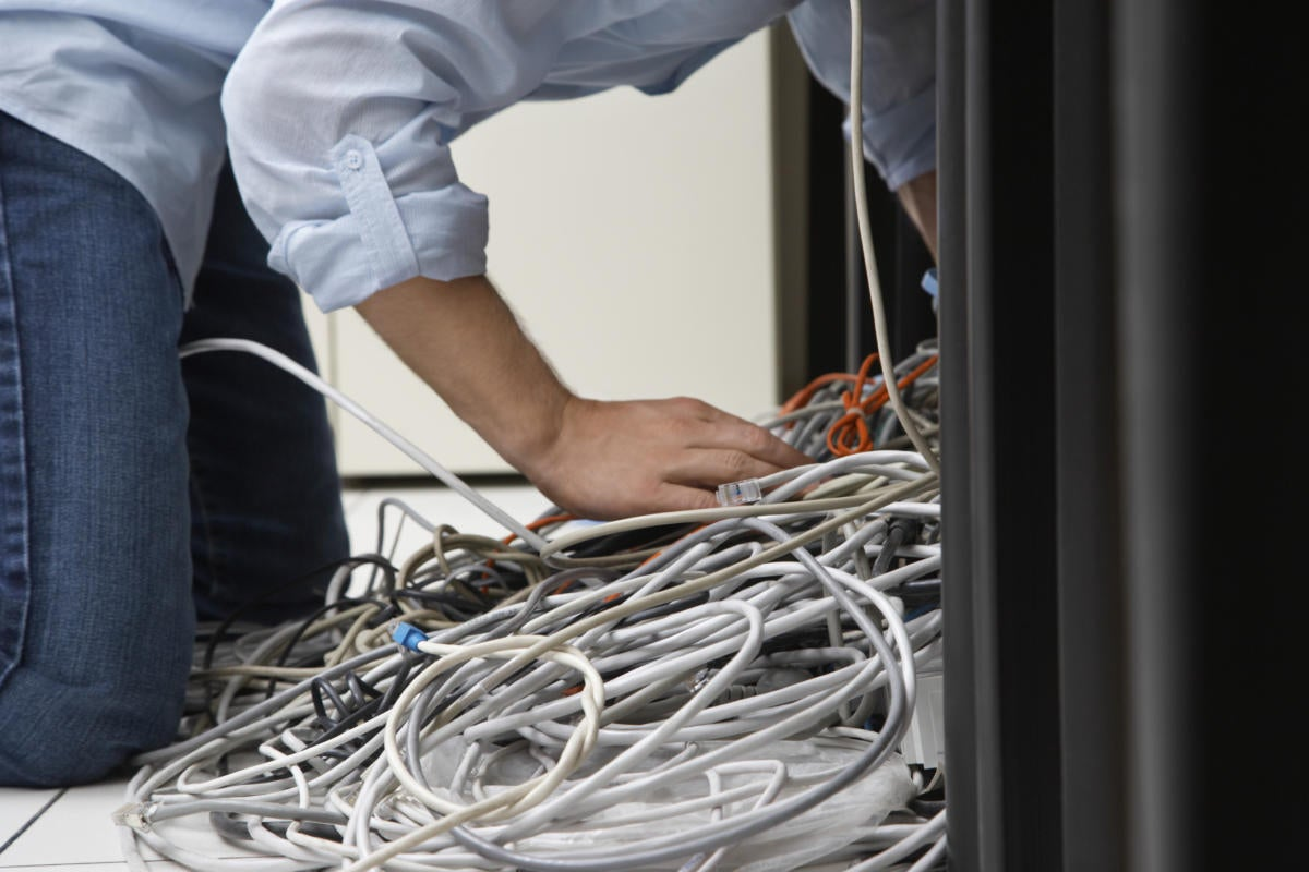 tech guy untangling network cables under desk