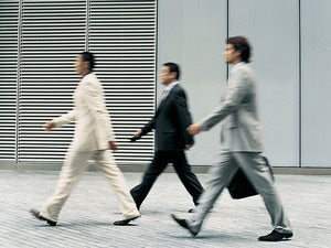 three suits walking