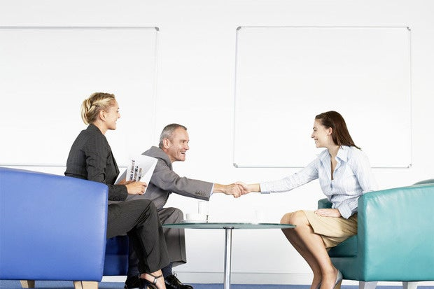 man and women executives sitting in office shaking hands and interviewing