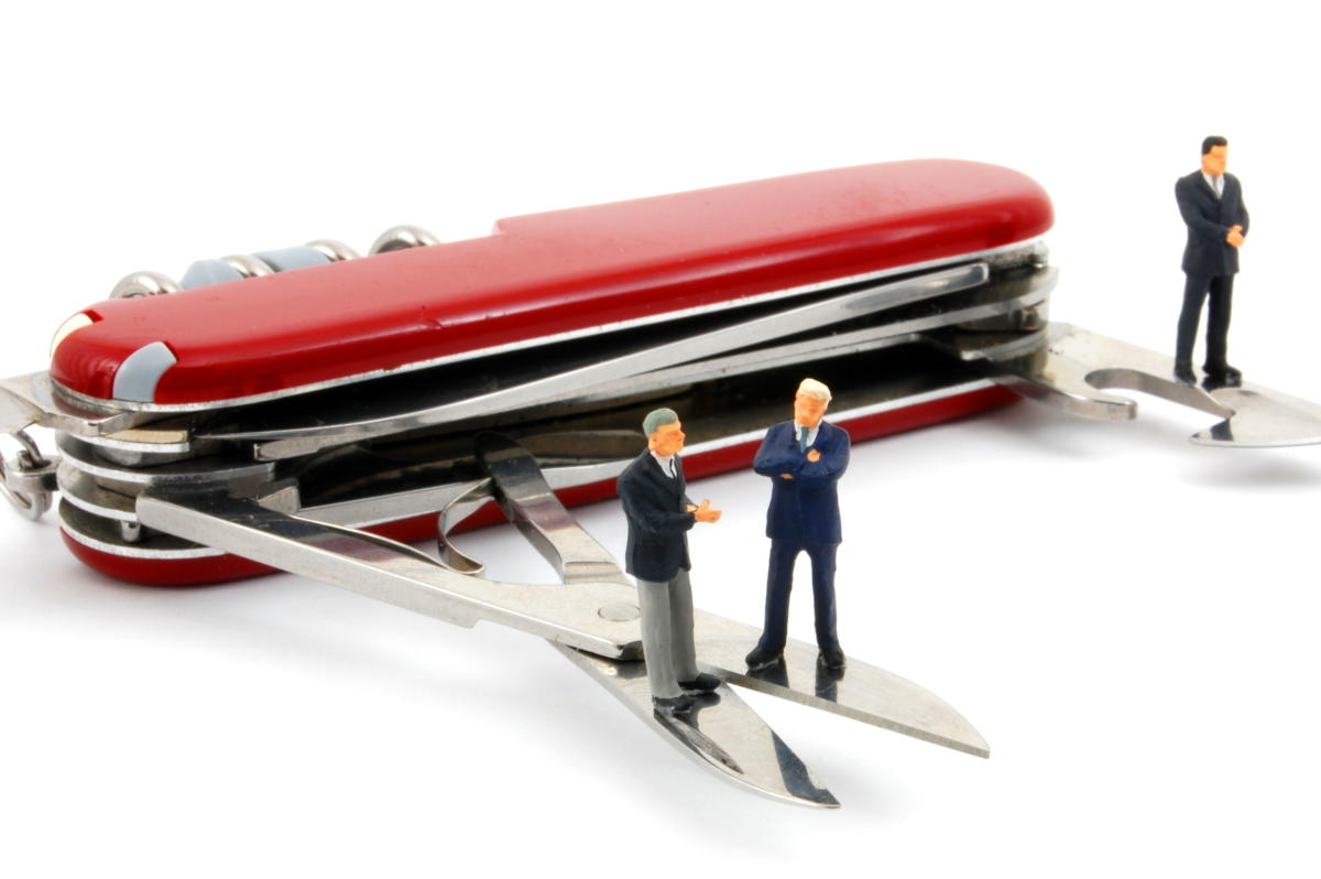 red swiss army knife with miniature business men