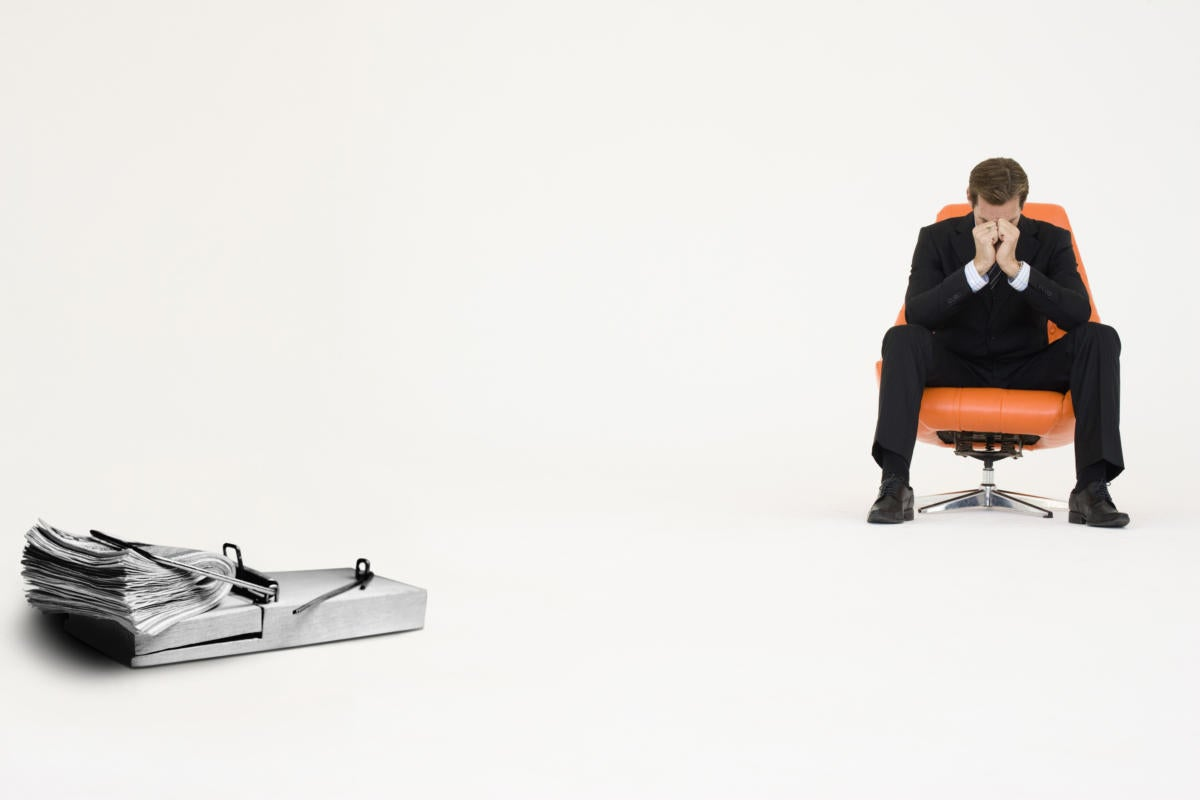 Man looking worn out in mod orange chair with a wad of cash in a mouse trap