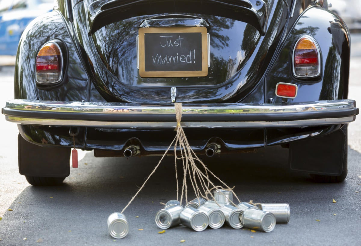 Vintage VW bug with just married cans dragging behind car