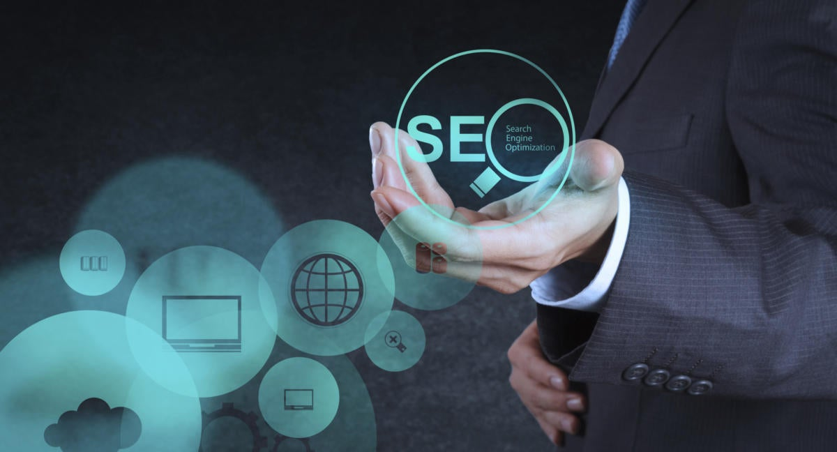 Torso of man holding SEO magnifying glass for search