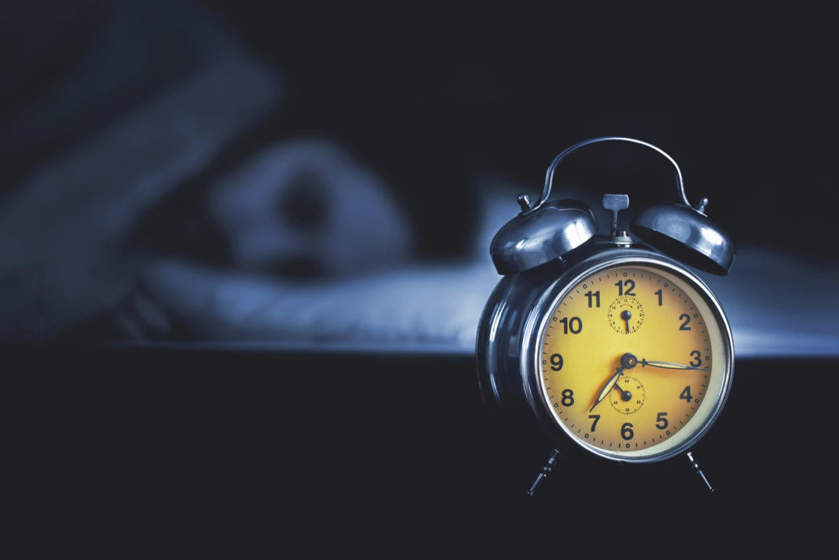 woman sleeping with yellow alarm clock in dark room
