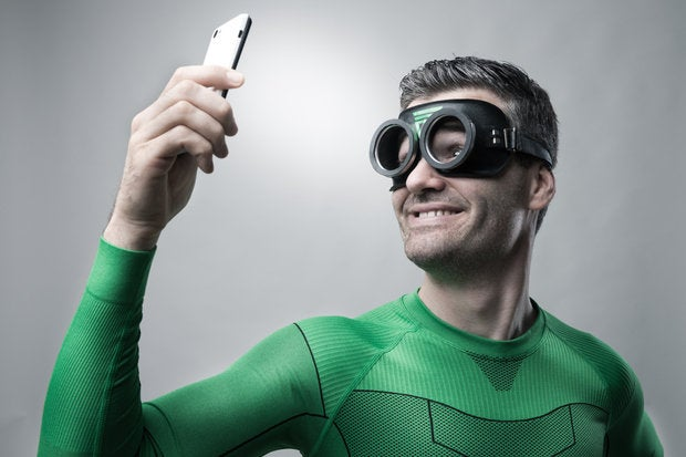 man in green superhero outfit wearing goggles taking selfie on smart phone