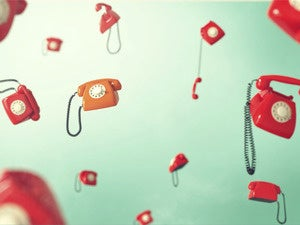 Flying red retro telephones on green background