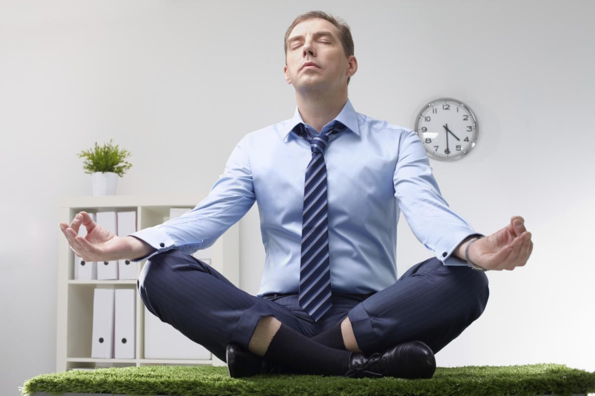 man sitting on desk doing yoga and meditating