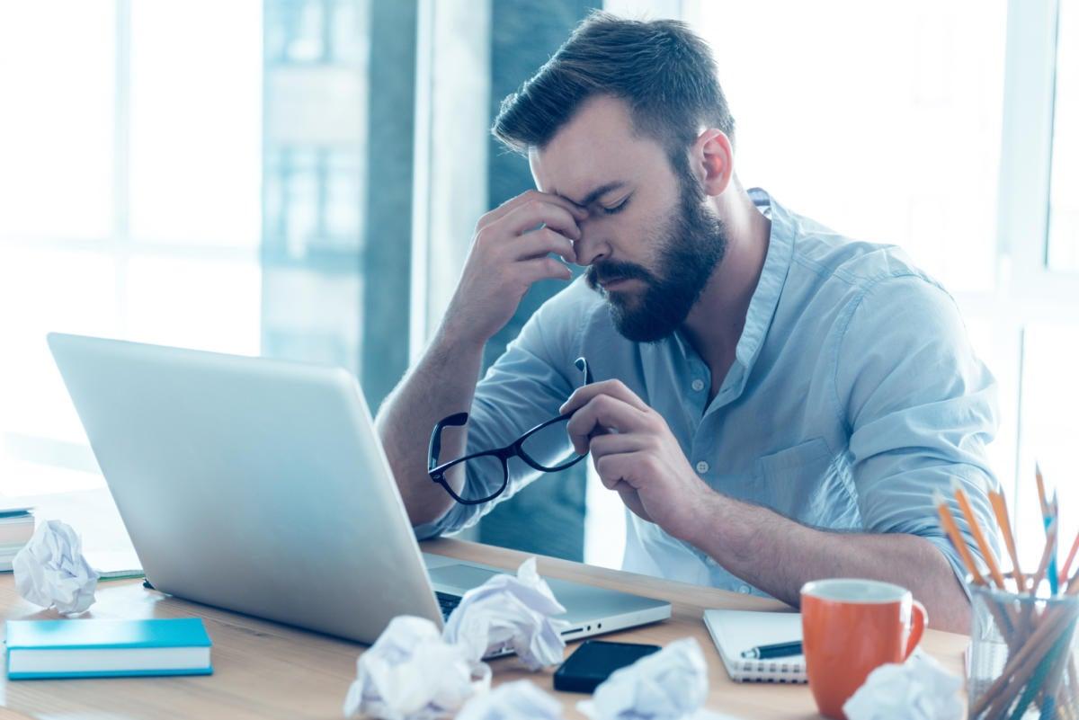 Man sitting at laptop looking tired