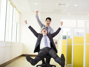 two young workers riding on office chair through office