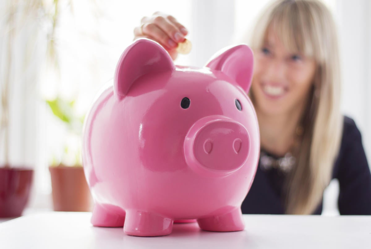 Woman smiling putting money in pink piggy bank