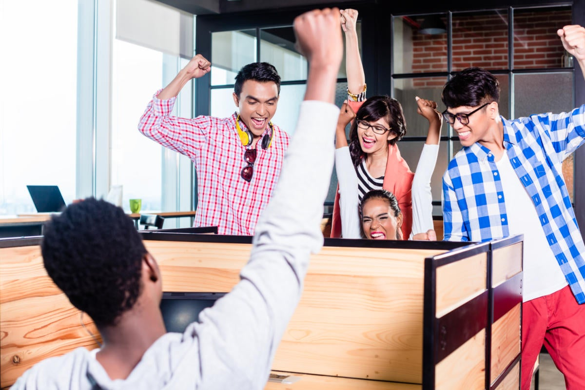 Group of millennials cheering in office